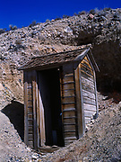 A long drop outhouse built over a mine shaft.  It will never need moving but watch out when the floor boards rot!  Eastern California Desert in Death Valley National Park, California.