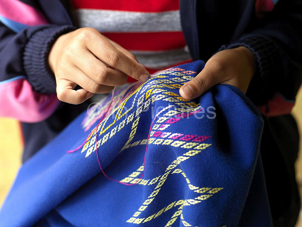 In the school holidays, a young Tai Dam girl embroiders her first sinh (traditional Lao skirt), Ban Na Mor, Oudomxay province, Lao PDR. She has been watching and learning from her mother and other female family members since she was a young child.