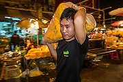 19 OCTOBER 2012 - BANGKOK, THAILAND:   A man carries a load of marigolds he bought through the Bangkok Flower Marker. The Bangkok Flower Market (Pak Klong Talad) is the biggest wholesale and retail fresh flower market in Bangkok. The market is busiest between 3:30AM and 6AM.      PHOTO BY JACK KURTZ