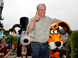 © Licensed to London News Pictures. 28/06/2013. Bristol, UK. Nick Park of Aardman Animations who created Gromit when he was a student, with some of the Gromit Unleashed sculptures in Bristol.  From Monday 1st July, Bristol will be home to 80 iconic giant Gromit sculptures as our public arts trail Gromit Unleashed takes to the streets.  The 5 foot high sculptures which have been painted by artists will be placed in various locations around Bristol and will eventually be auctioned for charity.  All proceeds from Gromit Unleashed will benefit Wallace & Gromit's Grand Appeal, the Bristol Children's Hospital Charity.  26 June 2013.<br /> Photo credit : Simon Chapman/LNP