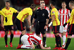 Referee Jon Moss speaks to Watford's Adrian Mariappa (centre right) as Stoke City's Charlie Adam kneels on the ground during the Premier League match at the bet365 Stadium, Stoke.