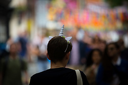 © Licensed to London News Pictures . 26/08/2016 . Manchester , UK . A man wearing a unicorn headband on Canal Street in Manchcester's Gay Village for 2016 Manchester Gay Pride Big Weekend . Photo credit : Joel Goodman/LNP