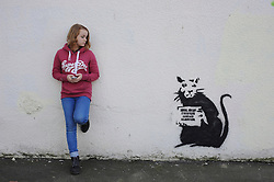 "© Licensed to London News Pictures. 31/10/2015. Folkestone, UK. HOPE WALTERS  age 13  stands next to a new artwork by the artist BANKSY, next to the location of a BANKSY piece that was removed. The Artwork pokes fun at the removal of the last piece which was called ""Art Buff"", which was of an old lady, and says ""IF FOUND PLEASE CONTACT ALASTAIR. Alastair Upton is the Chief Executive of the Creative Foundation who as called for the picture to be returned to the town. Photo credit:Grant Falvey/LNP"