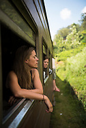 On the train to Ella, Sri Lanka, a woman visiting from Denmark leans out the open window, eyes momentarily closed, on a beautiful day in the Sri Lankan countryside (April 9, 2017)