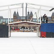 Amsterdam, 27-11-2013. Werklui zijn druk bezig met de opbouw van de ijsbaan op het Museumplein.  Vanaf vrijdag 29-11-2013 gaat de geheel vernieuwde schaatsbaan voor het publiek open. Er is nu ook een ophaalbrug over de baan. Hollandse schaatspret voor iedereen met het Rijksmuseum als decor.