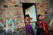 Poonam, 11, (left) and her sister Jyoti, 12, (right) are having an afternoon break before leaving to attend afternoon tuition lessons with a teacher living close to their newly built home, in Oriya Basti, one of the water-contaminated colonies in Bhopal, central India, near the abandoned Union Carbide (now DOW Chemical) industrial complex, site of the infamous '1984 Gas Disaster'.