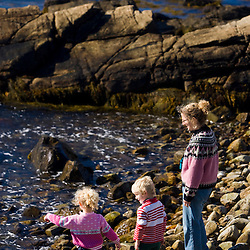 A mom and two girls (ages 4 and 6) play on a cobble beach in Biddeford, Maine.