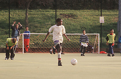 Multiracial group of young children playing game of football on artificial pitch,