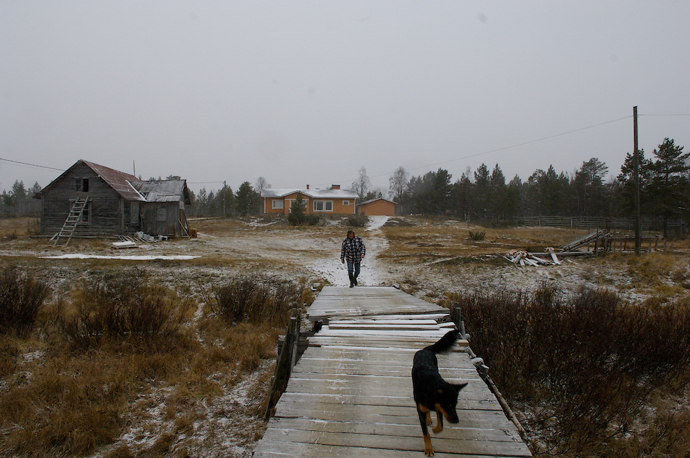 Lemmonoki, FINLAND.  October 20, 2007- Uule Sara, 35, and dog Vota cross the bridge from his home.  His grandparent?s home (middleground left) remains but his modern day home supplants the old ways and more simple living.