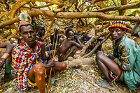 Hamer tribe people at a bull jumping ceremony, which is a rite of passage to initiate a boy into manhood.  In the center is the boy who will be jumping the bulls. The other men are being painted up to participate in the ceremony. Omo Valley, Ethiopia.