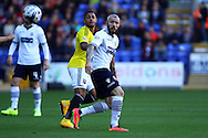Bolton Wanderers' Kevin McNaughton clears the ball ahead of Brentfords' Andre Gray. Skybet football league championship match, Bolton Wanderers v Brentford at the Macron stadium in Bolton, Lancs on Saturday 25th October 2014.<br /> pic by Chris Stading, Andrew Orchard sports photography.