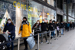 © Licensed to London News Pictures. 12/04/2021. London, UK. Shoppers queue to enter a branch of John Lewis on Oxford Street. From today gyms, non essential retail and theme parks can reopen following the easing of lockdown restrictions. Photo credit: George Cracknell Wright/LNP
