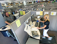 8/29/08 Omaha, NEB.Among a sea of cubicles, Zandra Hooks (right), clicks her mouse and talks on the phone all while walking on a treadmill Friday morning..Also on a treadmill is Kirk Hurley (left).Mutual of Omaha has 4 Walkstations in their customer-service area. Workers spend part of their shift walking on a treadmill while answering calls..Chris Machian/For the NY TImes..CONTACT INFO FOR Zandra Hooks.402 202 0870.Kirk Hurley: 402 305 5901