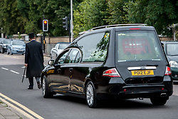 © Licensed to London News Pictures. 25/08/2015. London, UK. The hearse carrying actor, Stephen Lewis, who played Inspector Cyril 'Blakey' in the sitcom TV series, On The Buses leaving the church. Lewis died on Wednesday the 12th of August 2015 aged 88. The funeral was held today, the 25th August 2015 at Our Lady Of Lourdes Church in Wanstead, east London. Photo credit: Pete Maclaine/LNP
