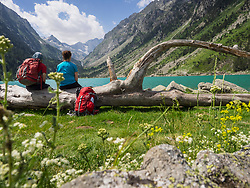 Hikers admiring scenic view of mountain and Gaube Lake, Cauterets, France