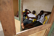 Young men sitting in a wooden shack in Accra, Ghana.