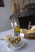 Table with alioli, spanish green olives, bread and oil, salt, pepper and vinegar, with a rural chimney behind, in an ibizan restaurant located on the beach, specialized in sea food and other typical and traditional dishes, Ibiza, Balearic Islands, Spain - Photo By Nano Calvo
