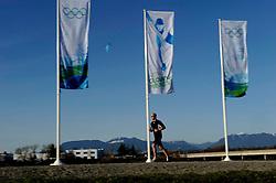 19-02-2010 ALGEMEEN: OLYMPISCHE SPELEN: AROUND OLYMPIC OVAL: VANCOUVER<br /> Banners, vlaggen olympic bergen vliegveld, hardloper jogger<br /> ©2010-WWW.FOTOHOOGENDOORN.NL