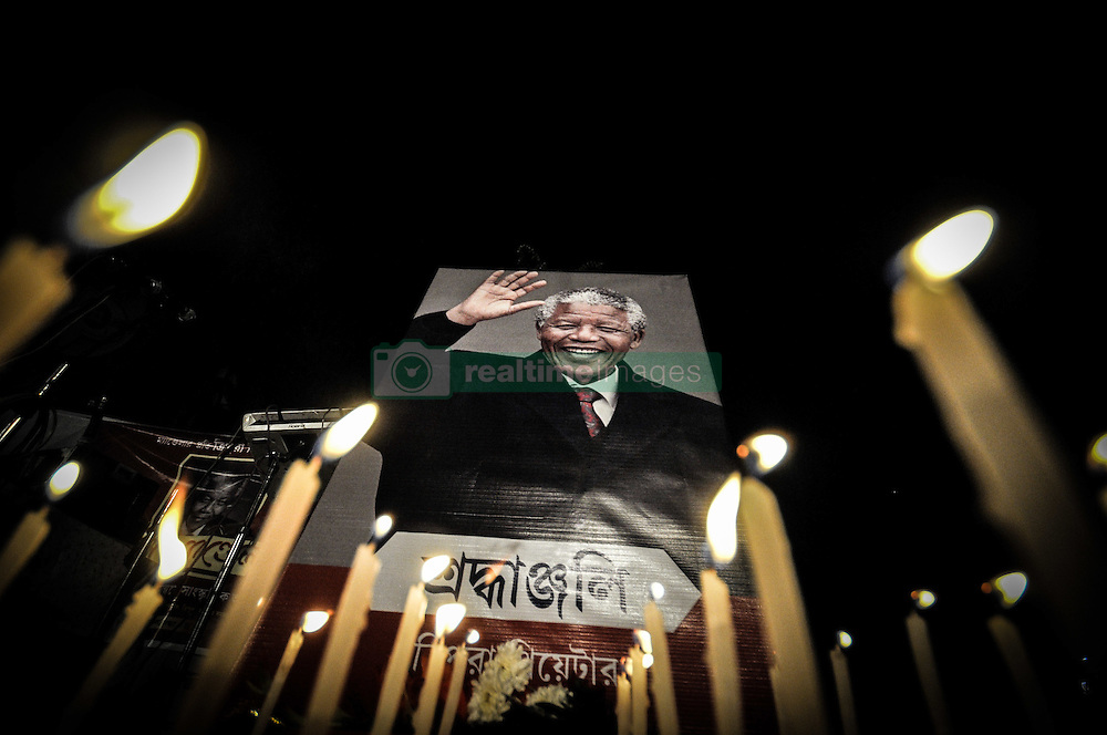 Dec. 20, 2013 - Agartala, Tripura, India - The Theatre people offers floral and candel  tributes in front of a portrait of Nelson Mandela in Agartala, capital of the North Eastern state of Tripura, India. Mandela, who died Thursday aged 95, became South Africaâ??s first black president after spending nearly a third of his life as a prisoner of apartheid. ..Photo: Abhisek Saha/NurPhoto (Credit Image: © Abhisek Saha/NurPhoto/ZUMAPRESS.com)