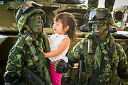 """11 JANUARY 2014 - BANGKOK, THAILAND: A Thai girl looks at Thai special forces soldiers during an Army open house on Children's Day. The Royal Thai Army hosted a """"Children's Day"""" event at the 2nd Cavalry King's Guard Division base in Bangkok. Children had an opportunity to look at military weapons, climb around on tanks, artillery pieces and helicopters and look at battlefield medical facilities. The Children's Day fair comes amidst political strife and concerns of a possible coup in Thailand. Earlier in the week, the Thai army announced that movements of armored vehicles through Bangkok were not in preparation of a coup, but were moving equipment into position for Children's Day.      PHOTO BY JACK KURTZ"""