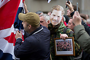 A face mask of army veteran Prince Harry is worn by a right-wing supporter of the anti-Islam activist Tommy Robinson real name Stephen Yaxley-Lennon and former leader of the now-banned English Defence League outside the Central Criminal Court The Old Bailey on 23rd October 2018, in London, England. Around a thousand gathered in the street specially cordoned off by City of London police as Robinson appeared before Nicholas Hilliard, the recorder of London, for a contempt hearing at the Old Bailey during which he was again bailed before the case was referred to the attorney general.