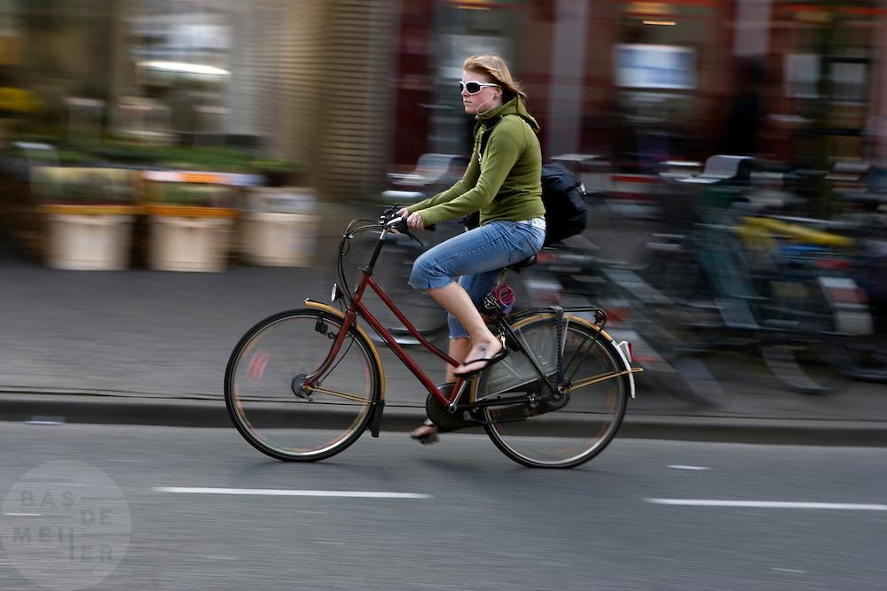 Een meisje fietst met een MP3 speler op door Leiden