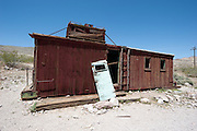 A railroad building sits abandoned in the desert.