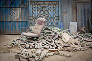 A broken office chair stands amongst a large pile of empty beer bottles that are all covered in dust next to a busy road on the 13th of March 2020 in Kathmandu, Nepal.