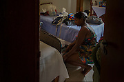 A woman is seen organizing clothes inside a hotel room in Mariana that is housing displaced people by a flood. On november 5th, a mining waste dam failed causing a flood of mud over Bento Rodrigues, a district of the city of Mariana, in the brazilian state of Minas Gerais.