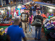 23 AUGUST 2014 - BANGKOK, THAILAND: Tourists walk between vendor stalls on Sukhumvit Road near Soi 5 in the Nana section of Bangkok. The Thai military junta, formally called the National Council for Peace and Order (NCPO), has ordered street vendors off of the sidewalks in an effort to bring order to Bangkok's chaotic sidewalks. Vendors have complained that the new regulations are hurting them economically but largely complied with the military orders.        PHOTO BY JACK KURTZ