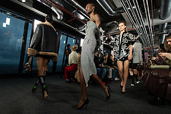 © Licensed to London News Pictures. 15/02/2020. London, UK.  London Fashion Week Fall Winter 2020 - David Koma runway show at The Leadenhall Building - models on the catwalk.  A cloudy sky can be seen through the window - the weather is stormy and windy.  Photo credit : Richard Isaac/LNP