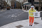 Road safety cut out person on empty deserted streets on Shaftesbury Avenue as the national coronavirus lockdown three continues on 5th March 2021 in London, United Kingdom. With the roadmap for coming out of the lockdown has been laid out, this nationwide lockdown continues to advise all citizens to follow the message to stay at home, protect the NHS and save lives, and the streets of the capital are quiet and empty of normal numbers of people.