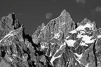 The moon sets behind the high peaks of the Tetons in Grand Teton National Park, Jackson Hole, Wyoming.
