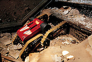 A fifteen-centimeter-tall robot scout, Schempf's Mini-Dora is intended to help police check out potentially dangerous situations. Unloaded from the back of a squad car, it could investigate buildings without risking the lives of police, as Schempf demonstrates by driving it up the front steps of an abandoned factory in a crumbling industrial section of Pittsburgh, PA. From the book Robo sapiens: Evolution of a New Species, page 145.