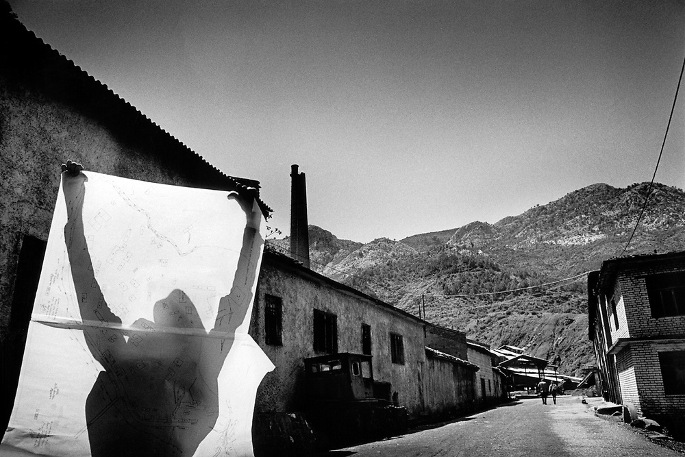 2/4: Man holding map by the copper mine / The town of Rubik in Northern Albania