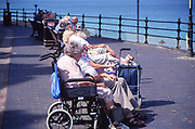 AMFXF1 Elderly people sitting on the promenade Cromer Norfolk England