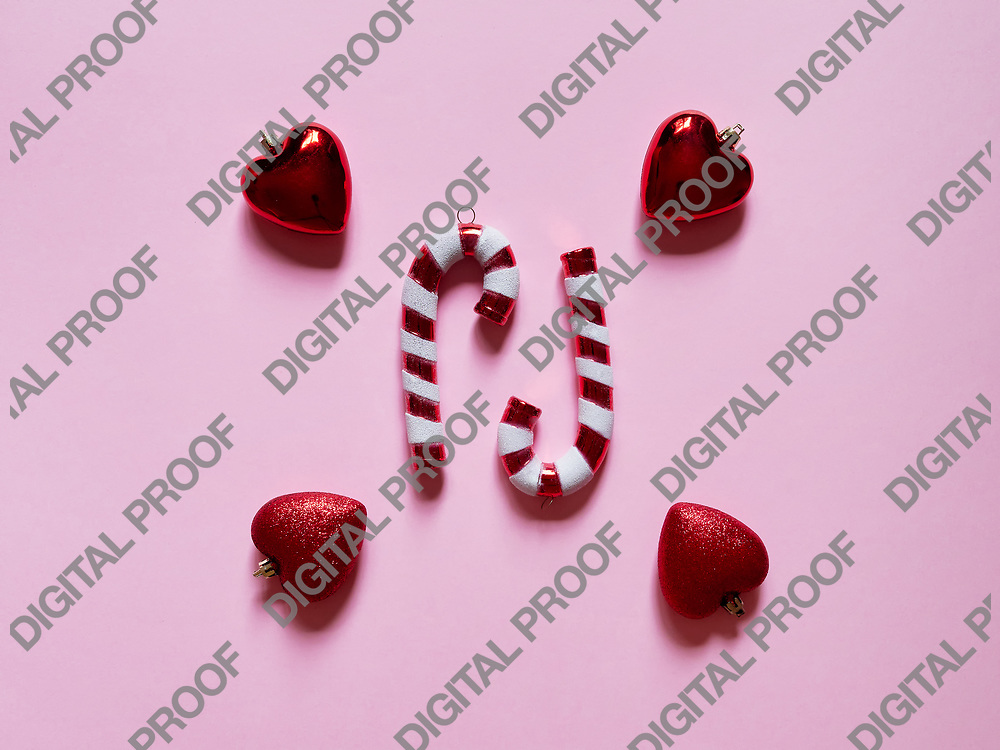 Christmas candy cane and hearts at studio above view over a pink background isolated flatlay