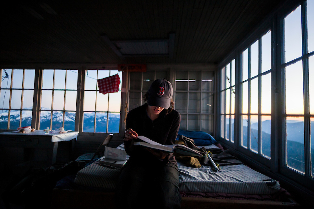 A young woman reads through the guest book at the Hidden Lake Peaks Lookout, North Cascades National Park, Washington.