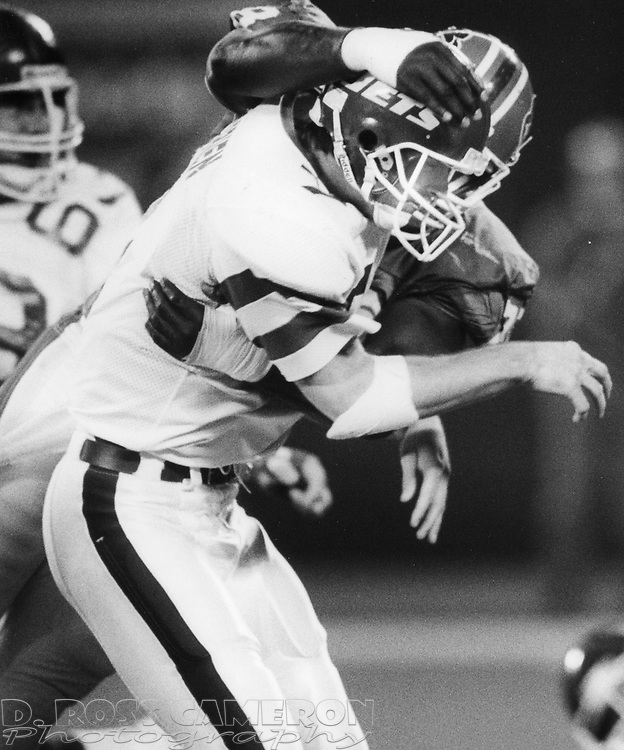 New York Jets quarterback Ken O'Brien (7) gets hit hard by Buffalo Bills defensive lineman Bruce Smith after dumping off a pass during the second quarter of an NFL football game, Monday, Oct. 17, 1988 at Giants Stadium in East Rutherford, N.J. O'Brien was sacked five times during the game, and the Bills won, 34-17. (D. Ross Cameron/The Express)
