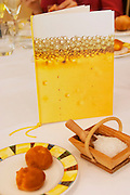A menu standing on a table for a champagne lunch and tasting with a small beaker basket of salt and a plate of bread on a white table cloth, Restaurant Les Berceaux, Patrick Michelon, Epernay, Champagne, Marne, Ardennes, France, low light grainy grain