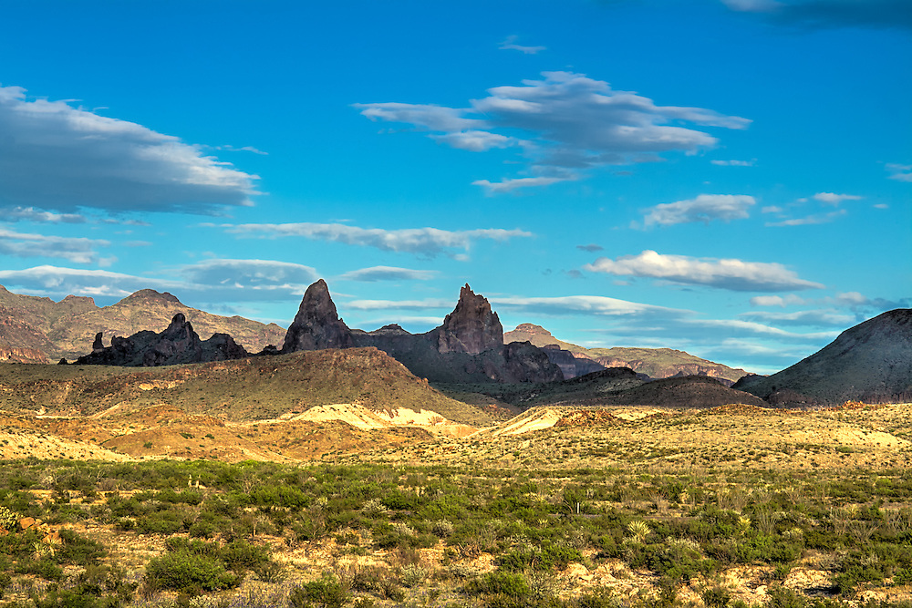 """One of the many great rock formations in the Chisos Mountains in Western Texas' Big Bend National Park and is known as the """"Mule Ear Peaks."""" These twin peaks  are formed from a part of a dike-like intrusion of relatively young rhyolite, and rise about 1040 feet (3,881 above sea level) above the desert floor."""