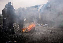 © Licensed to London News Pictures. 24/10/2016. Calais, France. Migrants burn belongings as they wait for the evacuation and demolition of the migrant camp in Calais, known as the 'Jungle'. French authorities have given an eviction order to thousands of refugees and migrants living at the makeshift living area of the French coast. Photo credit: Ben Cawthra/LNP