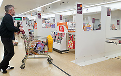 © Licensed to London News Pictures. 05/05/2020. London, UK. A shopper at a check-out in Sainsbury's supermarket. <br /> Partitions are installed in-between checkouts at Sainsbury's supermarket in north London to maintain the 2m distance rule to avoid the spread of COVID-19.  Photo credit: Dinendra Haria/LNP