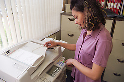 Young woman using photocopier in school office,
