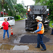 Sandy Propst, left, voices her concern about pot holes in the area as Edinburg Public Works employees Roland Perez, center, and Fernando Castaneda work on repairing a pot hole in the Lake James subdivision in Edinburg. Propst told the public works employees that a pot hole develops at that spot every couple of months. <br /> Nathan Lambrecht/The Monitor