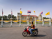 "30 DECEMBER 2013 - BANGKOK, THAILAND: A motorcycle taxi drives past Government House in Bangkok. Violence around the anti-government protest sites has escalated in recent days and several protestors have been hurt by small explosive devices thrown at their guard posts. As a result, protestors are fortifying their positions with sandbags and bunkers. Suthep Thaugsuban, the leader of the anti-government protests in Bangkok, has called for a new series of massive protests after the 1st of the year and said it the shutdown, or what he described was the seizure of the capital, would be the day when ""People's Revolution"" would ""begin to end and uproot the Thaksin regime.""          PHOTO BY JACK KURTZ"