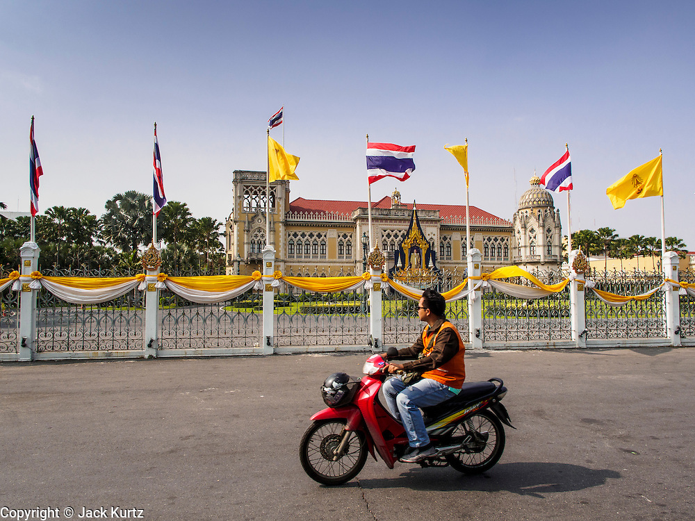"""30 DECEMBER 2013 - BANGKOK, THAILAND: A motorcycle taxi drives past Government House in Bangkok. Violence around the anti-government protest sites has escalated in recent days and several protestors have been hurt by small explosive devices thrown at their guard posts. As a result, protestors are fortifying their positions with sandbags and bunkers. Suthep Thaugsuban, the leader of the anti-government protests in Bangkok, has called for a new series of massive protests after the 1st of the year and said it the shutdown, or what he described was the seizure of the capital, would be the day when """"People's Revolution"""" would """"begin to end and uproot the Thaksin regime.""""          PHOTO BY JACK KURTZ"""