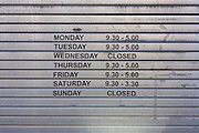 A small shop's business hours on lowered shutters in Harrogate, North Yorkshire.