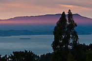 Beam of red sunlight and Mount Tamalpais at sunset over San Francisco Bay, California