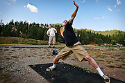 """William Everingham of Coeur d'Alene winds up for a """"hammer"""" frisbee golf drive on the first hole of the Cherry Hill frisbee golf course on Wednesday as Max Everingham stretches out. The frisbee golfers were warming up for competitive league play that began at 6:00 PM at the 15th Avenue park."""